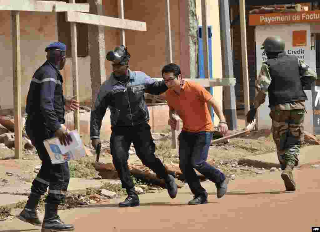 Lực lượng an ninh sơ tán một người đàn ông khỏi khu vực xung quanh khách sạn Radisson Blu ở thành phố Bamako, Mali. Những tay súng đã xả súng tại khách sạn sang trọng này, bắt 170 khách và nhân viên làm con tin làm ít nhất 18 người chết.