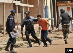 FILE - Malian security forces evacuate a man from an area surrounding the Radisson Blu hotel in Bamako, Nov. 20, 2015. Three Chinese railway executives were killed in the attack.Malian security forces evacuate a man from an area surrounding the Radisson Blu hotel in Bamako, Nov. 20, 2015.
