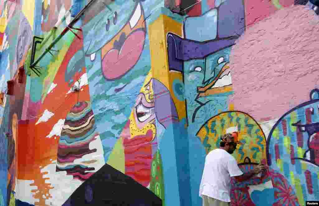 """Nghệ sĩ Brazil vẽ tranh trên tường Tomas """"Toz"""" Viana sửa lại lần cuối một tác phẩm trên tường một toà nhà tại Rio de Janeiro. Bức tranh trên tường này có diện tích 2.100 mét vuông."""