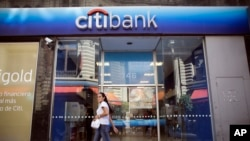 A woman walks by a Citibank branch in Buenos Aires, Argentina, March 17, 2015.