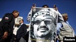 在约旦河西岸的一次集会中一名男子举着印有阿拉法特头像的海报