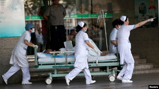 Medical personnel transport a victim of a factory explosion, at a hospital in Kunshan, Jiangsu province, August 2, 2014. An explosion killed at least 65 people and injured more than 120 at a factory in China that makes wheels for U.S. carmakers, including