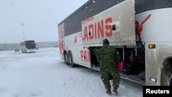 加拿大空军从中国撤侨的飞机抵达安大略的一个空军基地后,士兵把侨民的行李装上大巴车。(2020年2月7日)