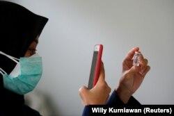 Seorang dokter mengambil gambar botol berisi vaksin Sinovac di fasilitas kesehatan kabupaten sebagai vaksinasi massal untuk Covid-19, di Jakarta, 19 Januari 2021. (Foto: Reuters/Willy Kurniawan)
