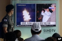 A South Korean army soldier watches a TV news program showing images published in North Korea's Rodong Sinmun newspaper of a recent North Korea ballistic missile launch and North Korean leader Kim Jong-un, at Seoul Railway station in Seoul, South Korea.