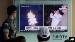A South Korean army soldier watches a TV news program showing images published Thursday in North Korea's Rodong Sinmun newspaper of North Korea's ballistic missile launch and North Korean leader Kim Jong-un, at Seoul Railway station in Seoul, South Korea, Aug. 25, 2016.