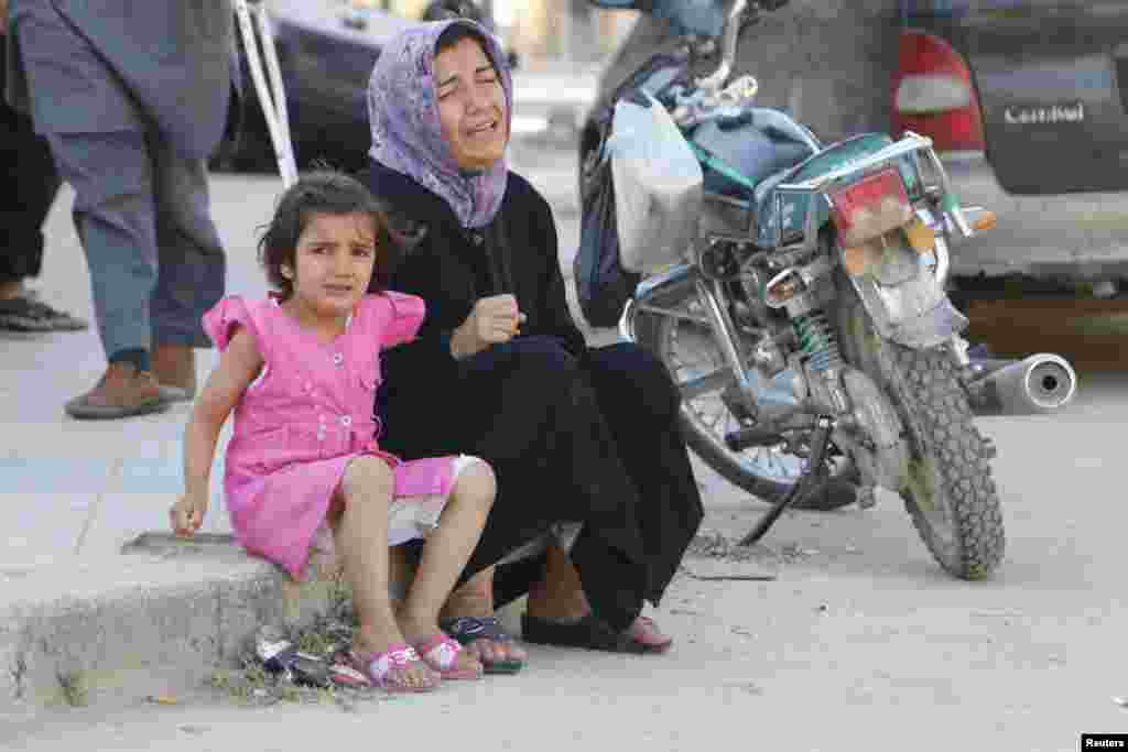 A woman and a girl react after, according to activists, two barrel bombs were thrown by forces loyal to  President Bashar Al-Assad, in Hullok neighborhood, Aleppo, May 1, 2014.