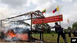 Seorang polisi Myanmar menyulutkan api ke tumpukan narkoba yang berhasil disita dan dimusnahkan pada acara Anti Penyelundupan Obat-obatan Sedunia, 26/6/2013.
