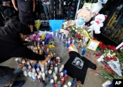 Fans of rapper Nipsey Hussle are seen gathered at a makeshift memorial in the parking lot of Hussle's Marathon Clothing store in Los Angeles, April 1, 2019.