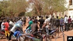 Des badauds contemplent les dégâts après un attentat au Mali.
