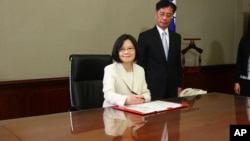FILE - Taiwan's President Tsai Ing-wen signs her first document at her new desk following the inauguration ceremony at the Presidential Office in Taipei, Taiwan May 20, 2016.