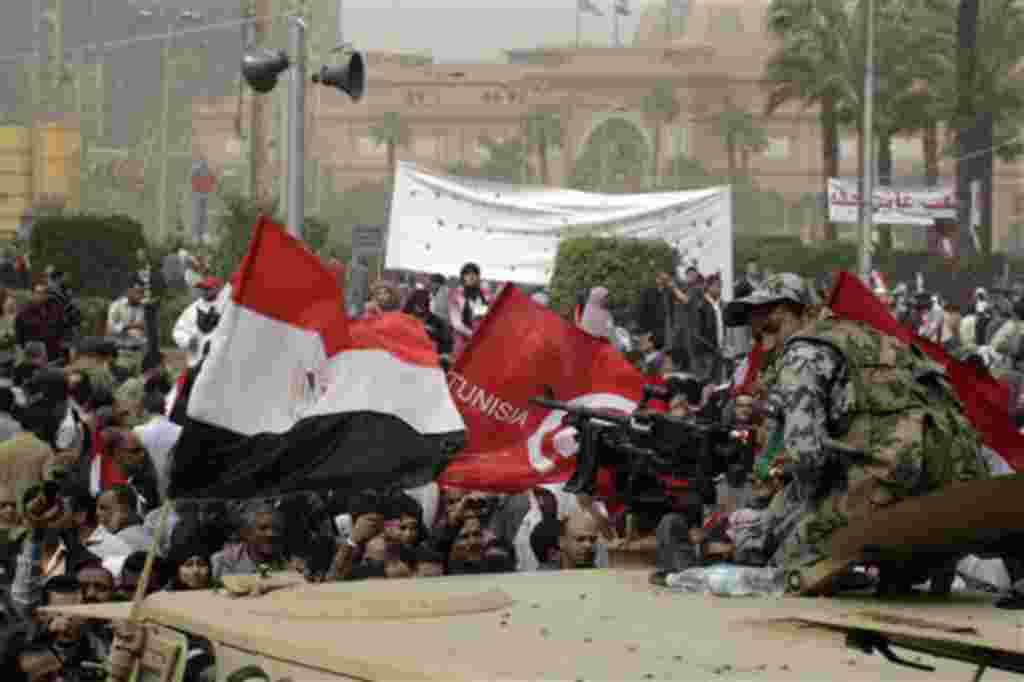 An Egyptian army soldier watches thousands of Egyptians gather at Cairo's Tahrir Square. February 25, 2011 (AP Photo/Amr Nabil)
