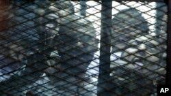 Các nhà hoạt động Ai Cập nhìn qua lưới của một cái lồng trong phòng xử án ở Cairo, Ai Cập, ngày 23 tháng 2 năm 2015.