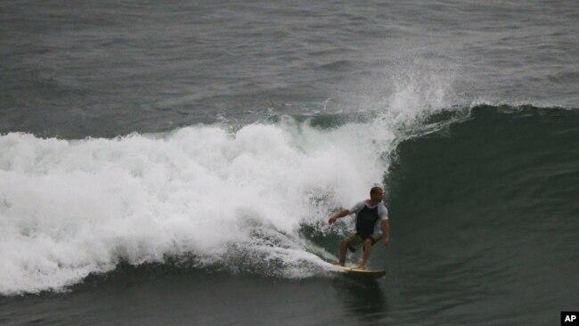 Un surfista monta una ola en Mazatlán, México, el martes 23 de octubre de 2018, antes de la llegada del huracán Willa.