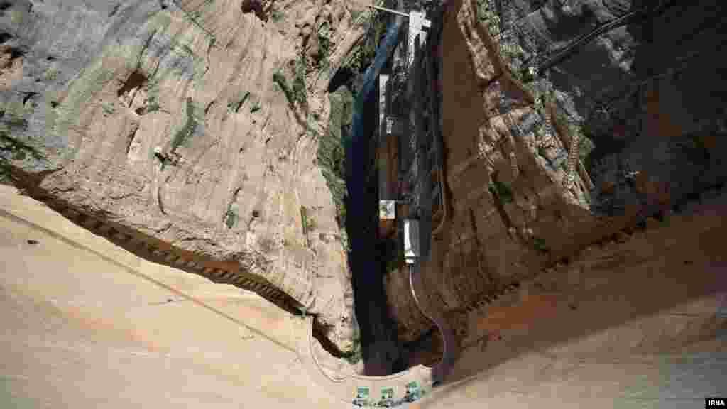 این عکس که از بلندی گرفته شده، کمی هراس انگیز است. اینجا سد کرخه است. در سی کیلومتری اندیمشک، برخی به تماشای سد بزرگ کرخه رفته اند. این سد بر روی رودخانه کرخه با ارتفاع ۱۲۷ متر است. کرخه را بزرگترین سد خاکی ایران و خاورمیانه می دانند. عکس: مهدی رشنو، ایرنا