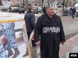 """莫斯科支持政治犯集会的一名参加者把自己装扮成囚徒,他胸前的字是""""腐败""""。(美国之音白桦拍摄)"""