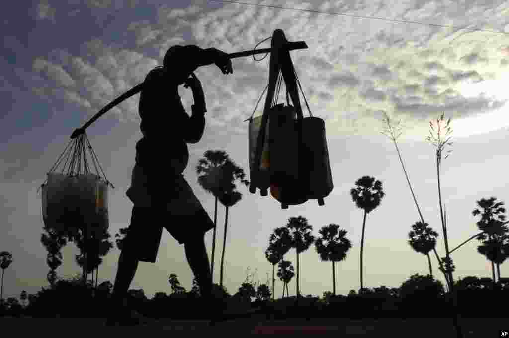 A man carrying plastic tubes full of palm juice at the Samroang village on the north side of Phnom Penh, Cambodia.