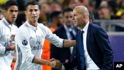 Cristiano Ronaldo de Real Madrid salue l'entraîneur de son équipe, Zinedine Zidane, après avoir ouvert le score lors d'un match de football de la Champions League entre le Borussia Dortmund et le Real Madrid à Dortmund, Allemagne, 27 septembre 2016.