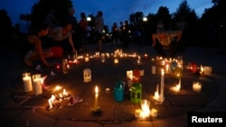 People take part in a vigil for victims of the fatal train disaster in Lac-Megantic, Quebec, July 12, 2013.