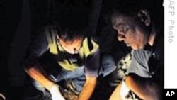 Bangladeshi bomb squad police officers collect evidence at scene of Dhaka bomb blast, 21 Oct 2009