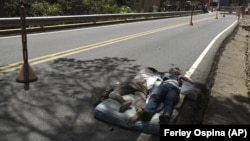 Venezuelan migrants sleep on a mattress on the side of the highway in Pamplona, Colombia, Wednesday, Oct. 7, 2020,(AP Photo/Ferley Ospina)