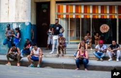 In this Jan. 6, 2017 photo, people use a public wifi hotspot in Havana, Cuba. Home internet came to Cuba in December 2016, in a limited pilot program