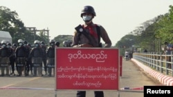 """FILE - Policeman stands behind a banner reading """"if this line is crossed, Myanmar police force will fire with live ammunition"""" during a protest against the military coup and to demand the release of Aung San Suu Kyi, in Naypyitaw, Myanmar, February 8, 2021."""
