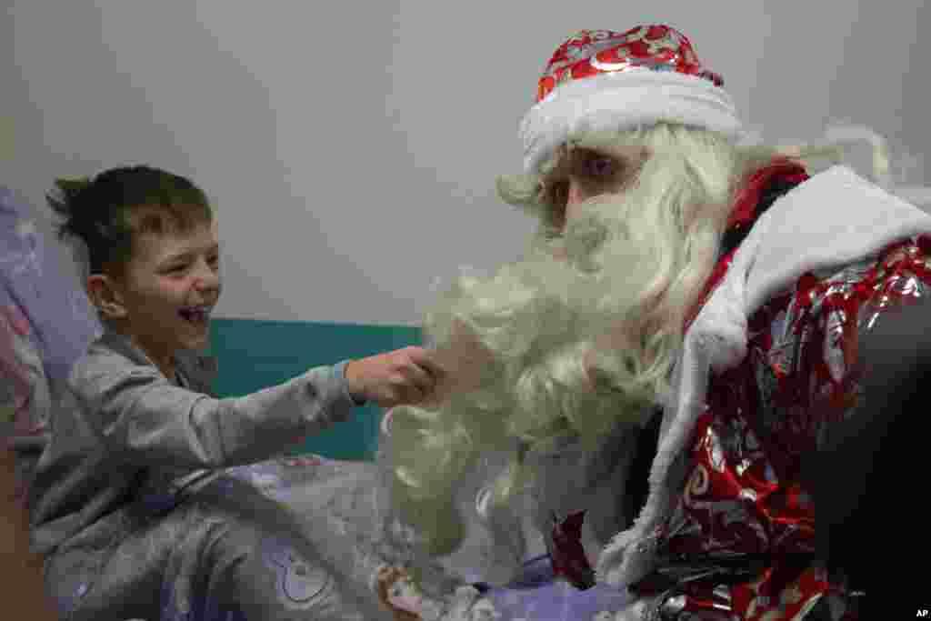 ក្មេងប្រុសម្នាក់ទាញពុកមាត់អ្នកជួយសង្គ្រោះគ្រាមានអាសន្នជនជាតិរុស្ស៊ីដែលស្លៀកពាក់ជាDed Moroz (Santa Claus) ក្រោយពេលគាត់បានឡើងលើជញ្ជាំងនៅមន្ទីរពេទ្យកុមារមួយក្នុងទីក្រុងមូស្គូ ប្រទេសរុស្ស៊ី។