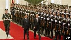 中国国家主席胡锦涛1月9日在北京人大会堂欢迎到访的韩国总统李明博(中右)