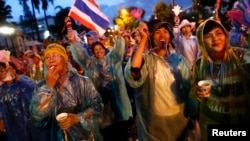 Anti-government protesters wear colorful rain coats as they block the road outside the Interior Ministry in Bangkok, Nov. 26, 2013.