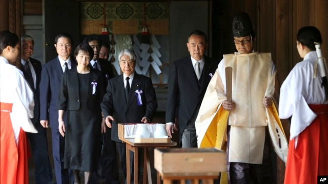 Japanese lawmakers visit the Yasukuni Shrine to pay respect to the war dead on the day of the 69th anniversary of the end of the World War II, in Tokyo , Friday, Aug. 15, 2014.