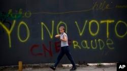 Una transeúnte pasa frente a un grafitti en Caracas que censura la elección presidencial del 20 de mayo, califcándola de fraude.