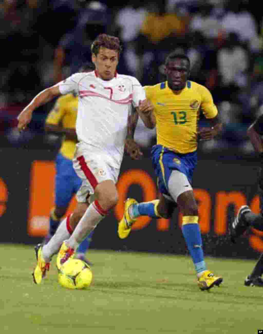 Tunisia's Youssef Msakni (R) challenges Mbanangoye Bruno Zita of Gabon during their African Cup of Nations Group C soccer match at Franceville stadium in Gabon January 31, 2012.