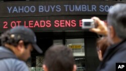 A news headline about the Tumblr sale to Yahoo scrolls on a building in New York's Times Square, May 20, 2013.