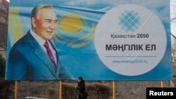 A woman walks past a poster depicting Kazakhstan's President Nursultan Nazarbayev in Almaty, Feb. 16, 2015.