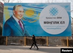 A woman walks past a poster depicting Kazakhstan's President Nursultan Nazarbayev in Almaty, Feb. 16, 2015.