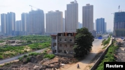 FILE - A man rides his bicycle past a partially demolished building in the middle of a street next to new residential construction sites in Xi'an, August 14, 2013. Some worry that, in pursuit of economic opportunities, Xi'an is trying to do too much too fast.