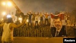 Para pendukung presiden Mesir terguling, Mohamed Morsi, berdiri berjajar di barikade yang mereka dirikan untuk memisahkan diri dari kora Nasr, timur Kairo (27/7). Demonstran pro-Morsi terus melanjutkan aksi mereka, mengabaikan perintah militer untuk segera membubarkan diri dan mengakhiri aksi duduk.