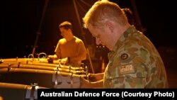 A RAAF Aircraft Armament Technician installs the laser guided system to a bomb in the Middle East Region.