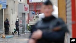Un militaire en armes sécurise le périmètre du lieu où a eu lieu une attaque djihadiste au moment où des pompiers, arrière-plan, s'y déploient dans la banlieue parisienne Saint-Denis, 19 novembre 2015. (AP Photo / Christophe Ena)