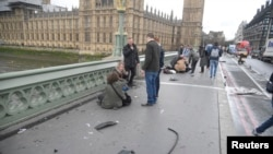 Injured people are assisted after an incident on Westminster Bridge in London, March 22, 2017.