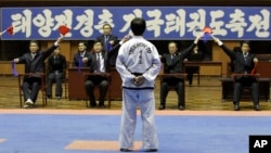 "FILE - A North Korean participant in a national Taekwondo festival is judged in front of a sign in Korean that reads ""National Taekwondo Festival for Celebrating Day of the Sun"" at the Taekwondo Hall in Pyongyang, North Korea, April 7, 2012."