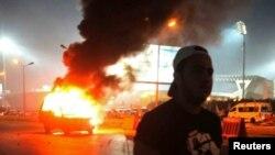 Một cổ động viên đứng gần chiếc xe cảnh sát bị cháy trong khi xô xát diễn ra giữa các cổ động viên và lực lượng an ninh trước sân vận động ở ngoại ô thủ đô Cairo, 8/2/15