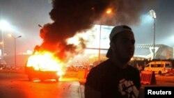 Un supporter de football marche près d'une voiture de police en feu après des affrontements entre les forces de police et des supporters, au Caire, Egypte, le 8 février 2015.