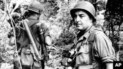 In this undated file photo, Associated Press photographer Horst Faas is shown on assignment with soldiers in South Vietnam.