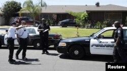 非洲裔美國人羅德尼.金的屍體被發現在家中的游泳池底﹐洛杉磯警員在他的屋外調查。