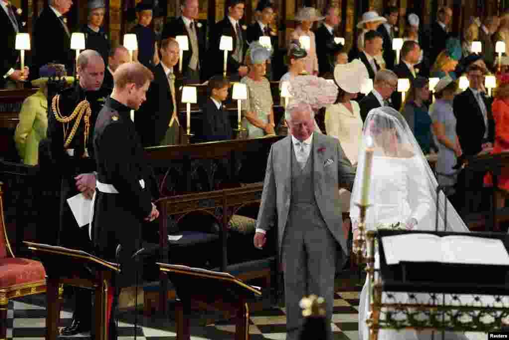 梅根·馬克爾在威爾士親王的陪伴下走向哈里王子。 (2018年5月19日)