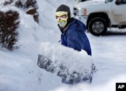 In Maine with the temperature at 3 degrees Fahrenheit, this man shovels snow wearing a face mask to guard against frostbite, January, 2014.