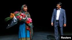 Malala Yousafzai bersama ayahnya, Ziauddin, di perpustakaan Birmingham, Inggris (10/10). (Reuters/Darren Staples)