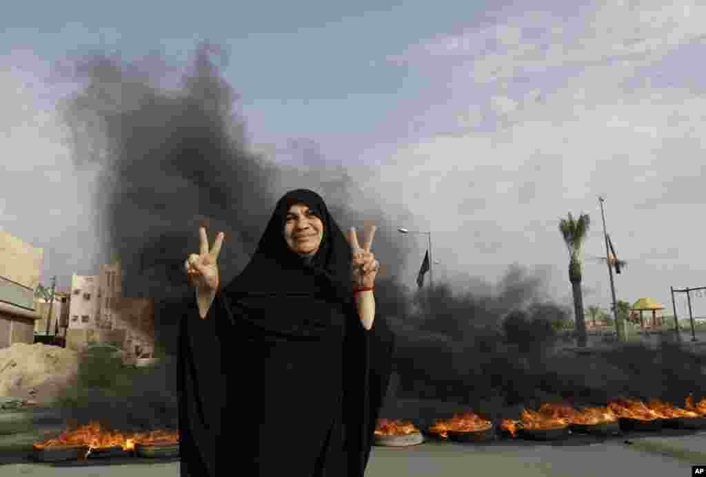 An anti-government protester poses for a photograph flashing the victory sign in front of burning tires on a road in the village of Dumistan, Bahrain, January 7, 2013.